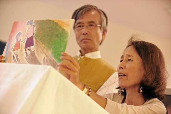 During Friday's Hiroshima remembrance at the Bangor Public Library,  Tomoko Ikeyima, right, and her husband Masanobu of Bar Harbor take turns reading a childrens' picture card story titled &quotGrandmother's Doll&quot  which recounts an elderly woman's recollection of Hiroshima bombing in 1945. (Bangor Daily News/John Clarke Russ)