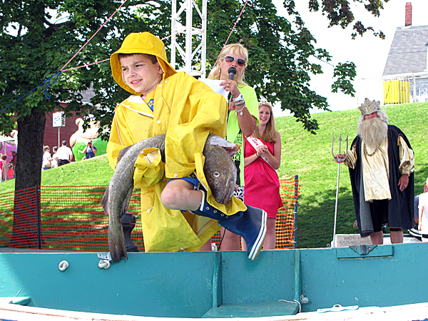 Dylan Baedke, 8, of Glen Ellyn, Ill., struggled to haul a dead cod into a rowboat on stage during the annual children's codfish carrying contest at the Maine Lobster Festival in Rockland on Sunday, Aug. 8, 2010. Contestants had to put on the oversized rain slicker, rain cap and rubber boots before touching the fish. Baedke had trouble picking up the slippery fish after it flopped to the ground but still walked away with a first-place prize because he was the only entrant in the third grader age class. BANGOR DAILY NEWS PHOTO BY KEVIN MILLER