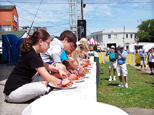 Contestants in the annual children's lobster-eating contest at the Maine Lobster Festival in Rockland quickly tear into their meals on Sunday while sitting on the festival's main stage. Jeanne Dugas, age 8, (far left) finished third in the contest. Residents of the New Orleans area, the Dugas family planned part of their New England vacation around the 63rd annual Maine Lobster Festival. BANGOR DAILY NEWS PHOTO BY KEVIN MILLER