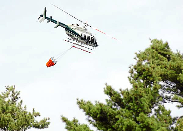 A Maine Forest Service helicopter equipped with a 230-gallon bucket of water makes several circles over a grassfire near I-95 a mile north of the Hogan Road exit in Bangor on Sunday, Aug. 8, 2010. (Bangor Daily News/Bridget Brown)