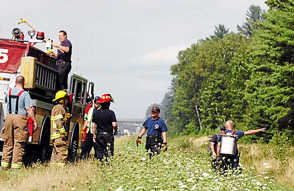 Bangor and Veazie Fire Deparment personnel prepare to fight a grassfire near I-95 a mile north of the Hogan Road exit in Bangor on Sunday, Aug. 8, 2010. (Bangor Daily News/Bridget Brown)