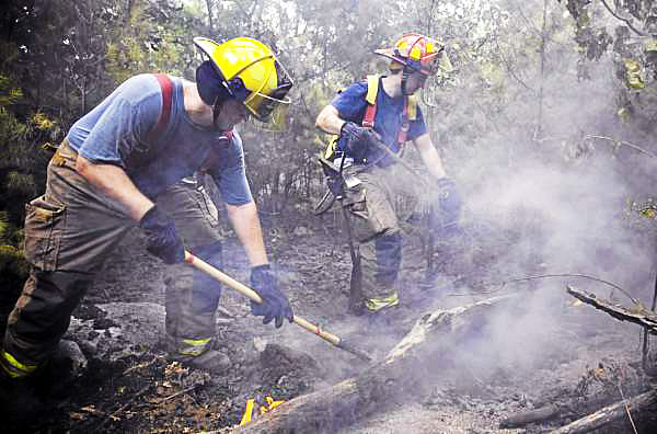 Veazie Firefighters (from left) Tyler Morrisson and Ken Roy work on some hot spots during a fire in the woods just north of the Hogan Road exit near I-95 in Bangor on August 8, 2010. The cause the fire was undetermined. (Photo courtesy of Monty J. Rand)