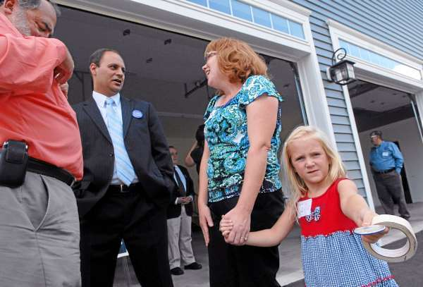 As her five-year-old daughter Julia Brown, far right,  handed out campaign buttons, Tammy Brown and State Sen. Tom Sawyer, far left, chatted with Congressional candidate Jason Levesque during a Levesque's campaign stop at the Brown home late Monday afternoon, August 9, 2010. (Bangor Daily News/John Clarke Russ)