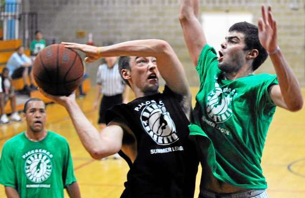 Brewer's Mike Cauley (in center) puts up a shot with Forever Young's Brandon Morey of Hampden pressuring during their college summer league game at Penobscot Job Corps Monday evening. Behind them  (lower left) is Forever Young's Blaine Meehan of Hampden. (Bangor Daily News/John Clarke Russ)