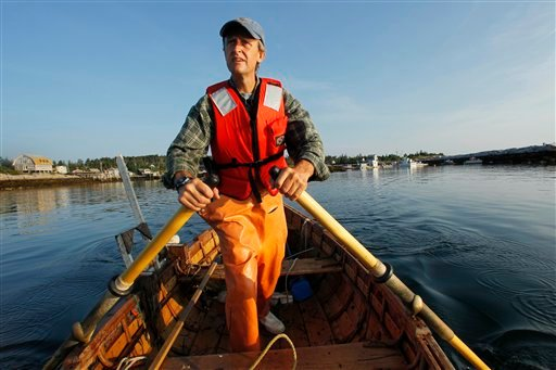 In this Wednesday, July 28, 2010 photo, lobsterman Nat Hussey rows out of the harbor on Matinicus Island, Maine.  Hussey is fishing the old-fashioned way,  rowing and hauling traps by hand in what he's calling his &quotzero-carbon lobstering project.&quot(AP Photo/Robert F. Bukaty)