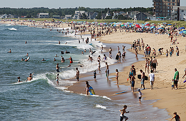 Swimmers and sunbathers are seen Wednesday, Aug. 11, 2010, in Old Orchard Beach, Maine. Strong rip currents and crowded beaches are making it a busy summer for lifeguards in southern Maine and New Hampshire. (AP Photo/Joel Page)