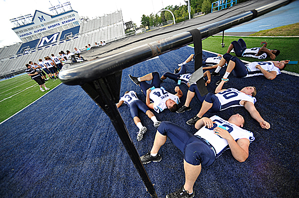 Members of the U Maine Black Bear football team find shade under a drill chute as other teammates have their team photos taken during the team's media day at Alfond Sports Stadium Wednesday afternoon, August 11, 2010. (Bangor Daily News/John Clarke Russ)