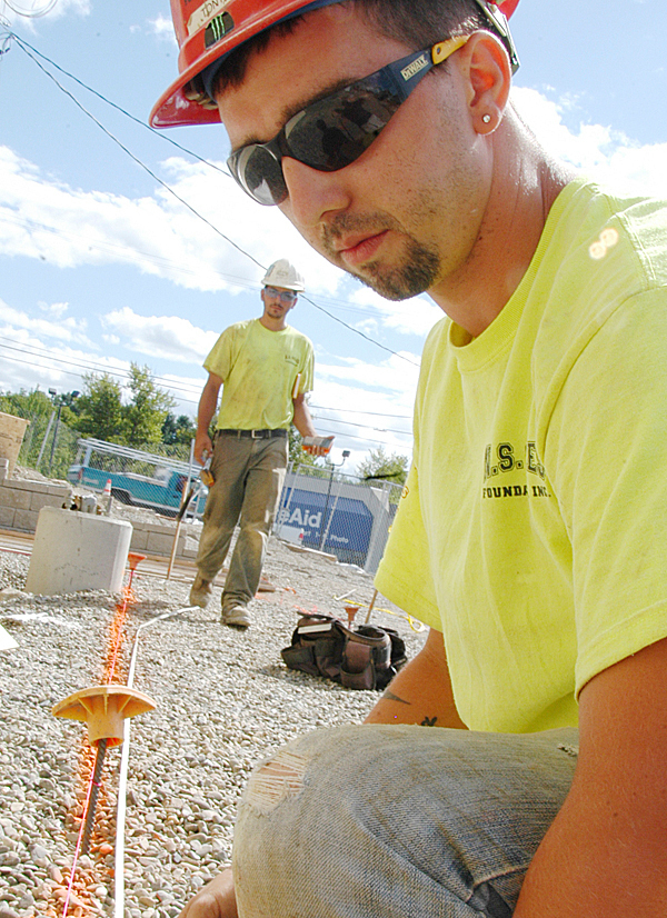 Tony DeRoche, 26, a form carpenter from Old Town working for N.S. Giles Foundations, Inc. of Bangor, measures a line that Rich Shay, 26, of Old Town helped him draw at the former Lake Mall site at Main Street and West Broadway in Lincoln on Wednesday. (Bangor Daily News/Nick Sambides Jr.)