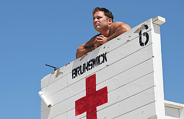 Lifeguard Wes Rhames keeps an eye on swimmers, Wednesday, Aug. 11, 2010, in Old Orchard Beach, Maine.  Strong rip currents and crowded beaches are making it a busy summer for lifeguards in southern Maine and New Hampshire. (AP Photo/Joel Page)