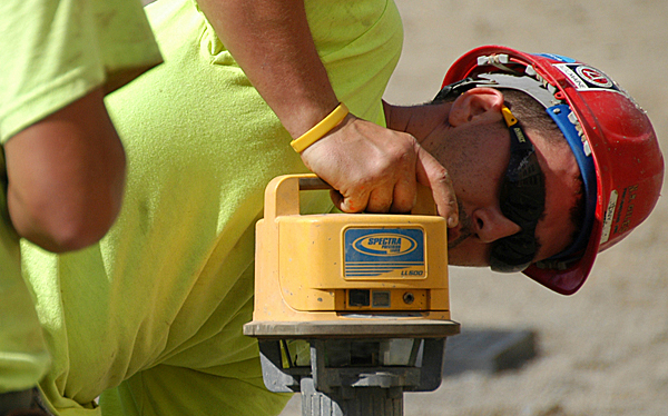 Tony DeRoche, 26, a form carpenter from Old Town working for N.S. Giles Foundations, Inc. of Bangor, uses a laser level to measure lines drawn for the placement of a foundation at the former Lake Mall site at Main Street and West Broadway in Lincoln on Wednesday.  (Bangor Daily News/Nick Sambides Jr.)