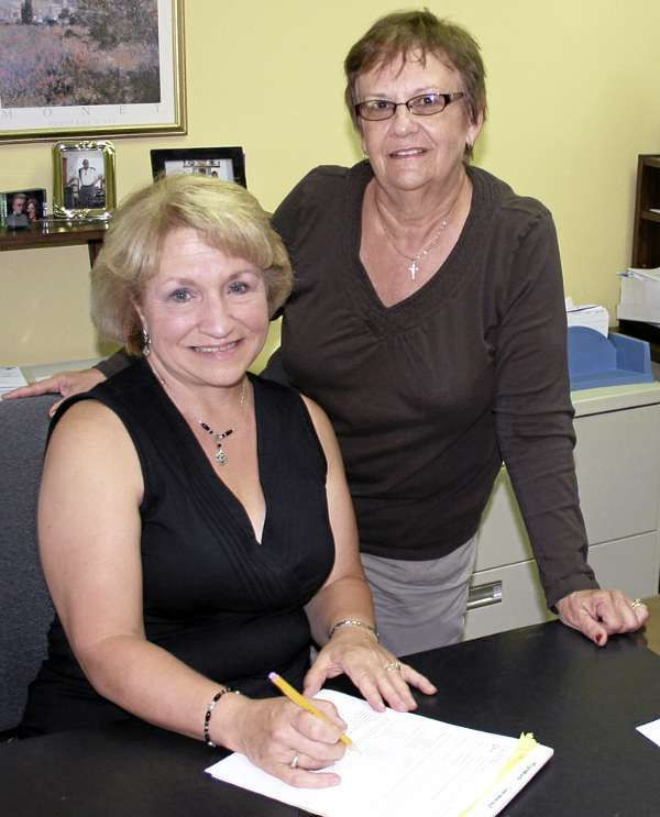 DONNA LISNIK, right, new principal at Presque Isle High School, has been busy this summer getting ready for the start of the 2010-11 academic year. The Presque Isle native replaces Eric Waddell, who resigned in April to become the new curriculum director of SAD 35 in Eliot. Lisnik had previously been the assistant principal at PIHS for five years. Here, she goes over some paperwork with Judy Cleaves, administrative assistant to the principal. The first day of school at PIHS is Wednesday, Aug. 18. (Staff photo/Scott Mitchell Johnson)