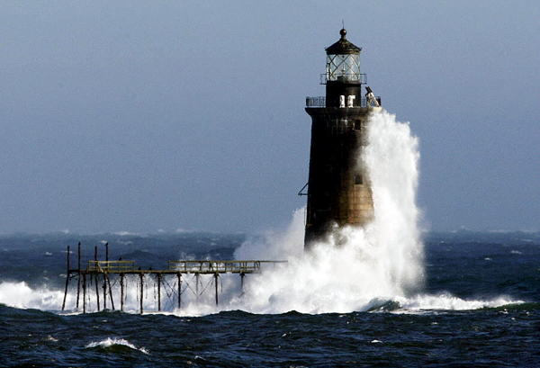 FILE - In this December 2009 file photo, heavy surf slams into the 72-foot-tall Ram Island Ledge Light, at the mouth of Portland Harbor, in Portland, Maine. The 105-year-old lighthouse is being auctioned by the federal government. (AP Photo/Robert F. Bukaty, File)