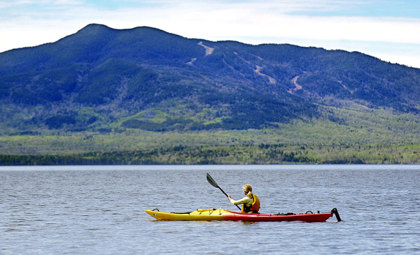 ** ADVANCE FOR MONDAY, JULY 23--FILE  **A kayaker paddles on Moosehead Lake at Lily Bay State Park, in this May 16, 2004, file photo in Beaver Cove, Maine. The 3,200-foot Big Moose Mountain rises near the lake's southwestern shore. Henry David Thoreau made his third and final trip to Maine's North Woods 150 years ago, traveling waterways and forests that shaped so many of his ideas about nature.  (AP Photo/Robert F. Bukaty/FILE)