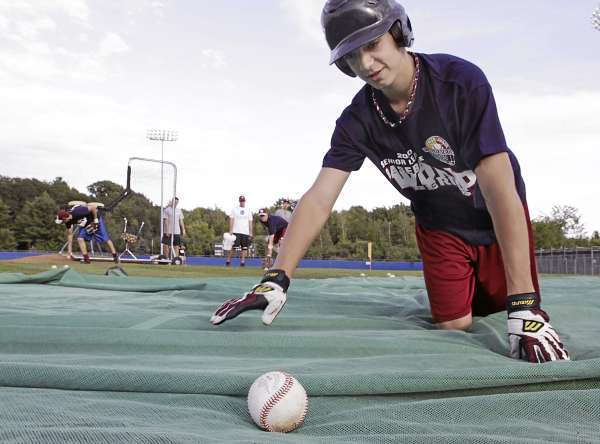 Tyler LaPlante collecst baseballs off the protective cover in front of home plate during batting practice at Mansfield Stadium Thursday, August 12, as the Bangor Senior League All Stars prep for the upcoming tournament.  Bangor Daily News/Michael C. York