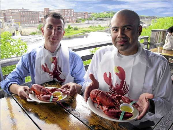 Programmer Ben Greeley (left) and Illustrator Robert P. Hernandez (right) hold lobster dinners at the Lobster Trap in Winslow Maine. Together, they have created an iPhone application that teaches people how to properly eat a lobster. Users can also find lobster restaurants based on their current GPS location and have lobster shipped to their home. (PHOTO CREDIT: PHOTO BY DANA BUSHEE HERNANDEZ)