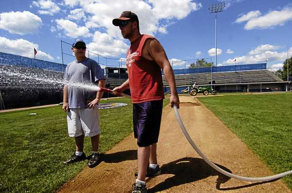 Grounds crew member Dana Leland, right, of Alton hoses newly installed sod as volunteer Chris Cosenze of Old Town sizes up the rest of the field at Shawn T. Mansfield Stadium Friday afternoon, August 13, 2010.  They joined other grounds crew Friday preparing the field for the upcoming Senior League World Series. The opening ceremony for the series takes place Saturday at 8 p.m and the games run Sunday, August 15 through Saturday, August 21. (Bangor Daily News/John Clarke Russ)