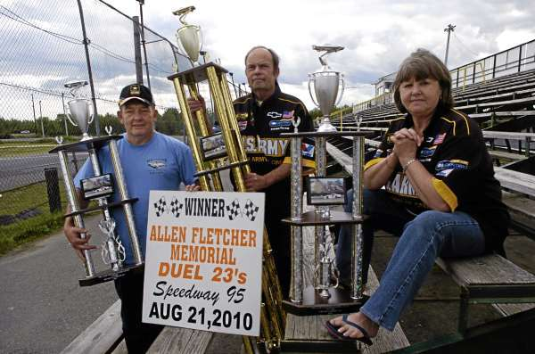 From left: Wally Gibbons of Bangor, Frank Oakes of Veazie and Penny Gibbons show off the trophies that will be handed to the winners of the Dysart's Late Models Allen Fletcher Memorial Duel 23's Race August 21 at 7.pm at Speedway 95. Long time friends of the late race car driver, Allen Fletcher who died in 2002, the trio also enlisted the help of the Army unit of Wally and Penny Gibbon's son,  Capt. Wally Gibbons III  in Fort Bragg, NC. The unit helped pay for the trophies that will be presented at the race. Photographed at Speedway 95 in Hermon, Maine August 12, 2010. (Bangor Daily News/John Clarke Russ)
