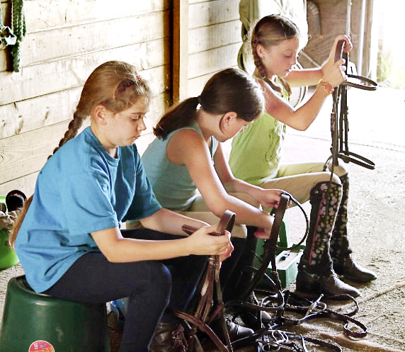 Jenny, 9, of Orono, Cassidy, 9, of Bradley, Emma, 9, of Glenburn, sit as they piece together their horses bridles on Aug. 11 during a lesson at the Wild Ivy Summer Horsemanship Camp at the Wild Ivy Farm in Bangor.  (Bangor Daily News/Aislinn Sarnacki)