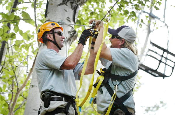 Jim McCormack (left) and Erik McClure, both of whom work at Sugarloaf and have been running the new zip lines, strap McCormack in for a ride near one of the ski lifts (right) on Thursday, Aug. 12, 2010 in Carrabassett Valley. (Bangor Daily News/Bridget Brown)
