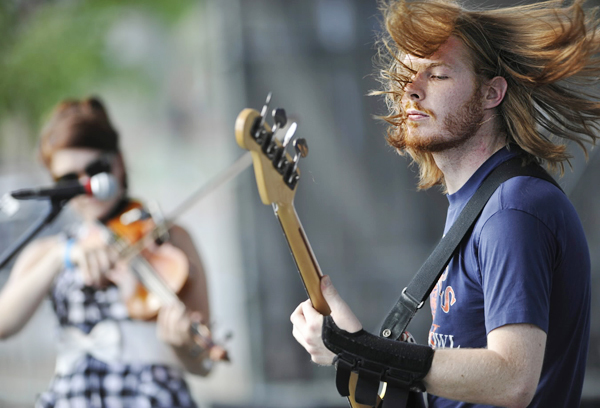 Guitarist Billy Lease, right, Sarah Welder (violin/ keyboards) and other members of the Louisville, KY-based band Cabin perform on Stage B as part of Friday's KahBang events on Bangor's waterfront(Bangor Daily News/John Clarke Russ)