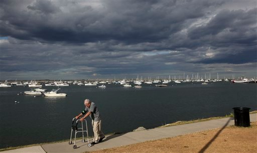 In this July 1, 2010 photo, a walker passes by Plymouth Harbor's privately owned boats in Plymouth, Mass. Ground fishing has virtually disappeared in this small port, and new fishing rules enacted in May have fishermen at New England's major ports worried their historic fishing communities could fade away, as well. (AP Photo/Julia Cumes)