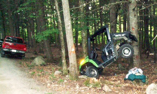 An Arctic Cat RTV with a dump bucket that was being driven by Tasha Barnes, 20, of Baileyville rests on a hemlock tree. Miss Barnes and two passengers were injured in the incident Saturday evening, August 15, 2010 in Danforth. (Photo Credit: Maine Warden Service)