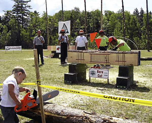 Kamoran Thurlow, a third generation logger from Lee, plays with his toy saw Saturday, as Chalma Greaterex, of Amherst, tries his luck in the bore cut competition at Forest Heritage Days. Watching Greaterex are from left: Stewart Hall, master of ceremonies; judges John Cullen and Steve Lawerson, and competitor Chris Maxim. Kamoran is the son of Spencer Thurlow and the grandson of Mike Thurlow, both of whom were judges at this year's logging competition. (Bangor Daily News Photo by Diana Bowley)