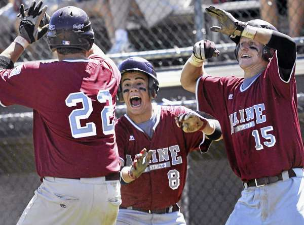 District Three players Nic Cota, (8), and Dylan Morris, (15), celebrate behind home plate as teammate Josiah Hartley, (22), scores the eighth run in their playoff game versus team Canada at Mansfield Stadium, Sunday, August 15, 2010. Bangor Daily News/Michael C. York