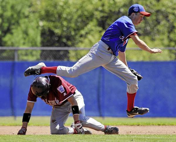 TEam Canada second baseman Dalen Mimeault leaps over District Three's Nic Cota, (8), after tagging him in  a rundown between first and second base in the fourth inning of their game at Mansfield Stadium, Bangor, Sunday, August 15, 2010.Bangor Daily News/Michael C. York