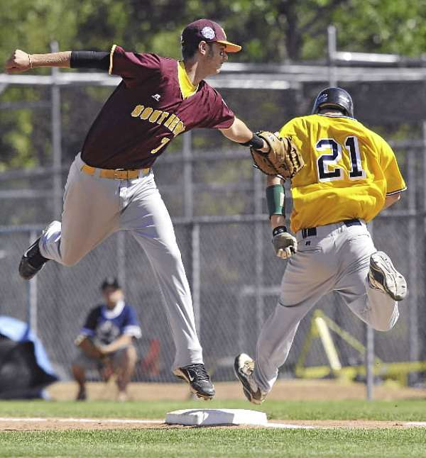 Southeast firstbaseman Matthew Rose, (7), tries to get the tag on West left fielder Brett Collins, (21), at first base after a high throw pulled him off the bag in the third inning of their game at Mansfield Stadium in Bangor, Maine, Sunday, August 15, 2010. Bangor Daily News/Michael C. York