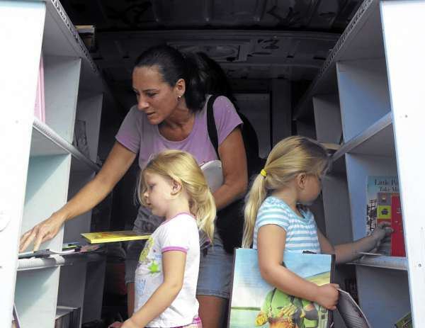 Christina Henderson of Houlton and her two children, Cindy and Emily Hannigan, look at books inside Bess the Book Bus on Tuesday, Aug. 17, at the Houlton Recreation Center. Each girl picked out two books from the mobile literacy outreach unit, which made its first stop to Maine during its ongoing national tour. The sunny yellow bus, which carries thousands of new and used children?s books, is driven by Jennifer Frances and her crew, a group that is based in Tampa, Fla.. Frances, 39, of Tampa, cashed in her 401(k) to establish the bus eight years ago. Each child picked out a few books and got a free bag to take them away in. Many of the titles were unfamiliar to the children, as the bus receives donations of newly published books that have yet to reach bookstores. BANGOR DAILY NEWS PHOTO BY JEN LYNDS