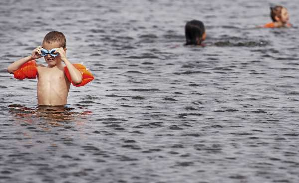 Ethan Read, 8, of Kingston, Mass. adjusts this goggles before exploring an underwater view Lake Wassookeag in Dexter where many families went to cool off Tuesday, Aug. 17, 2010. (Bangor Daily News/Bridget Brown)