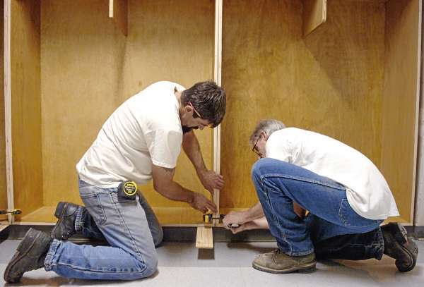 Gary Scott of Baileyville (left) and Bill Putnam of Houlton, both inmates at Charleston Correctional Facility, install new coat cubbies built through the facility's Woodshop Industry Program at Piscataquis Community Middle School in Guilford on Tuesday, Aug. 17, 21010. (Bangor Daily News/Bridget Brown)