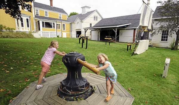 Sarah Marze, 9, (left) and her sister Lauren, 4, both of Canton, Connecticut turn a large capstain while playing in the yard of the Penobscot Marine Museum in Searsport Wednesday.  The museum received high national recognition and special accreditation. (Bangor Daily News/Gabor Degre)