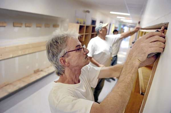 Bill Putnam of Houlton (left), an inmate at Charleston Correctional Facility, helps install new coat cubbies built through the facility's Woodshop Industry Program at Piscataquis Community Middle School in Guilford on Tuesday, Aug. 17, 21010. Also helping with the project, which included constructing and installing the two dozen sections made of oak with ash trim, are the program's manager Tom Sands and fellow inmate Gary Scott of Baileyville. (Bangor Daily News/Bridget Brown)