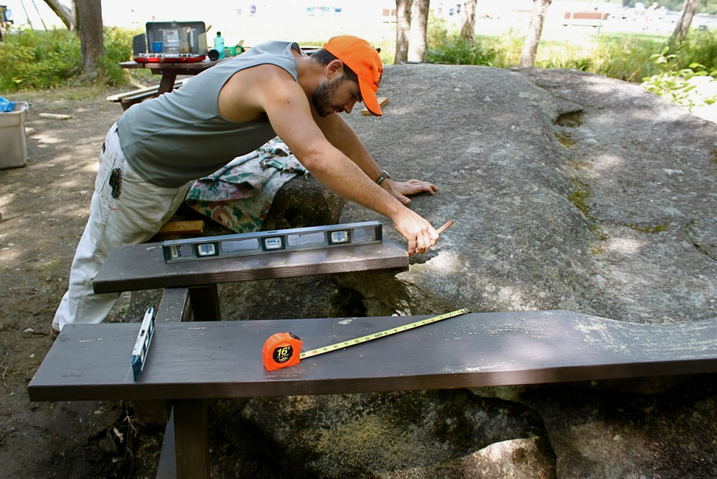 Wade Kavanaugh works on his third sculpture, a picnic table that hugs a glacial erratic, Aug. 17 by Sebec Lake in Peaks-Kenny State Park in Dover-Foxcroft. Kavenaugh will construct 12 of these sculptures, which are administered by the Maine Art Commission's Percent for Art program commisssioned by the Department of Conservation. (Bangor Daily News Photo by Aislinn Sarnacki)