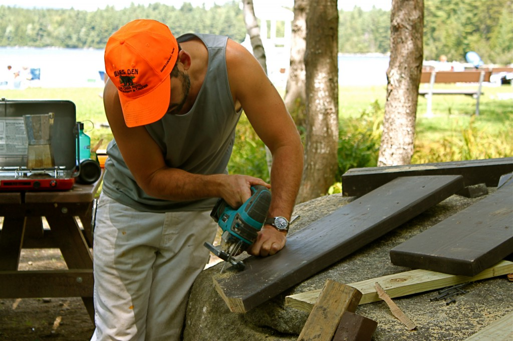 Wade Kavanaugh uses a portable saw to shape a plank for his third sculpture, a picnic table that hugs a glacial erratic, Aug. 17 by Sebec Lake in Peaks-Kenny State Park in Dover-Foxcroft. Kavenaugh will construct 12 of these sculptures, which are administered by the Maine Art Commission's Percent for Art program commisssioned by the Department of Conservation. (Bangor Daily News Photo by Aislinn Sarnacki)