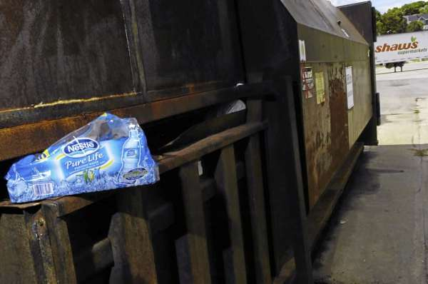 Bottled water packaging is wedged into a dumpster behind Shaws supermarket on Main Street in Bangor Thursday afternoon, August 12, 2010. A pair of men were recently spotted there after purchasing several cases of bottled water with food assitance money and then empyting the bottles in this loading dock area behind the supermarket so they could redeem the empty bottles for deposit money. (Bangor Daily News/John Clarke Russ)