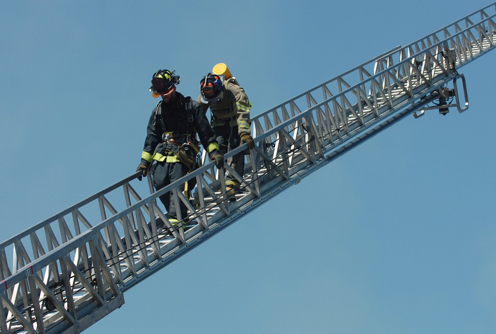 Firefighters descend the Dexter firetruck ladder after using it to fight a fire at the Big Apple store in Corinna on Thursday, Aug. 19, 2010. (Bangor Daily News/Bridget Brown)