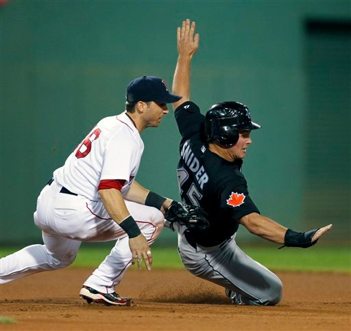 Boston Red Sox's Marco Scutaro, left, catches Toronto Blue Jays' Travis Snider between bases on a single by Fred Lewis in the tenth inning of a baseball game in Boston, Saturday, Aug. 21, 2010. (AP Photo/Michael Dwyer)