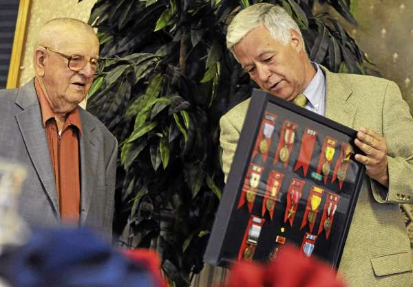 During his 90th birthday party at the Spectacular Events Center in Bangor Saturday,  a surprised Henry Stupakewicz of Hermon reacts as Congressman Mike Michaud, right,  presents him with more than a dozen medals he earned during his 26-year Army career which spanned World War II, the Korean Conflict and the Vietnam War. Stupakewicz had lost and misplaced the original medals and a friend and Michaud's staff managed to find replacements for most of them.  (Bangor Daily News/John Clarke Russ)