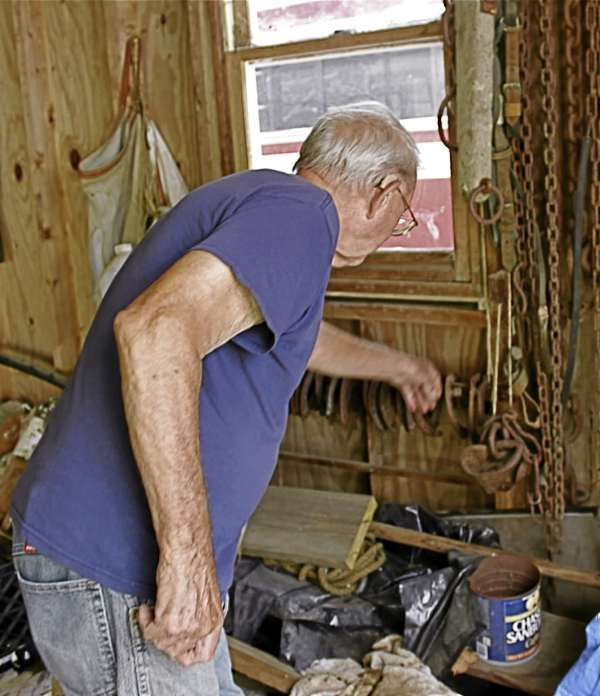 Roice Saunders, 88, retired farrier, reaches for a horseshoe on Aug. 20 in the garage at his home in Ellsworth. Buy Photo