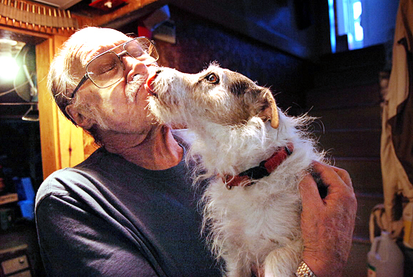 Don Barrett gets some affection from his dog &quotBuddy&quot who alerted Barrett to intruders early Monday at 3 a.m. at his home business, Mill Creek Rod & Gun in Orrington which he has run for 30 years. Barrett said Tuesday, Aug. 24, 2010 that the offender or offenders broke in through a basement window and got away with 12 guns. Maine State Police are investigating the burglary. (Bangor Daily News/Bridget Brown)