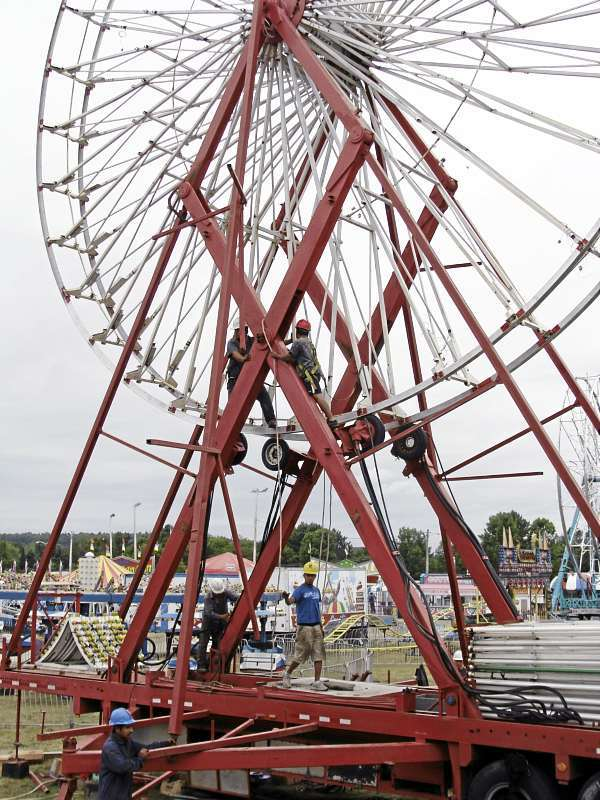 Employees with Smokey's Greater Shows assembled a ferris wheel Wednesday, Aug. 25, 2010 in preparation for opening day today of the Piscataquis Valley Fair. (Bangor Daily News Photo by Diana Bowley)