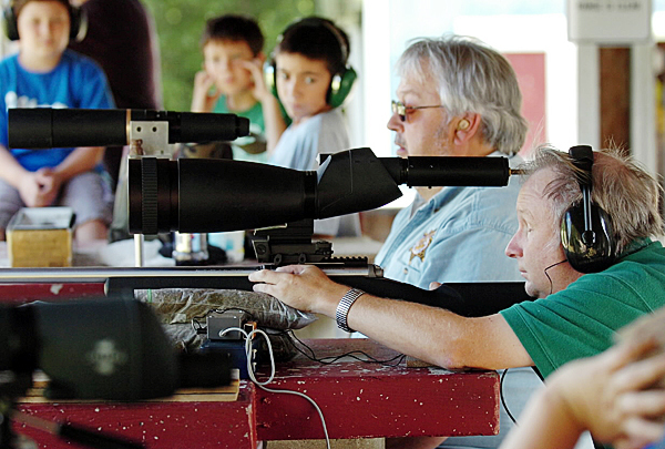 Using a scope he modified to help him &quotsee&quot a 200-yard target, James &quotJim&quot Miekka lines up a shot at the Orrington Rod & Gun Club on Tuesday, Aug. 24, 2010. Miekka, who lost his eyesight due to an emergency operation, still enjoys a day on the shooting range, a hobby he's had for more than 20 years. Looking on are (from left) Jacob Israel, 10, his brother Brandon Israel, 13, Patrick Goody, 12, and Goody's father and club president Jimmy Goody. (Bangor Daily News/Bridget Brown)