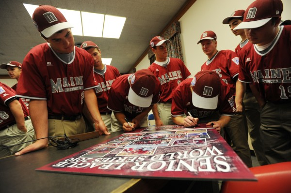 Members of the Maine District 3 baseball team gather around a poster to autograph it at Bangor City Hall on Thursday, Aug. 26, 2010 after they were honored for their second place showing in the Senior League World Series held in Bangor last week. (Bangor Daily News/Kevin Bennett)