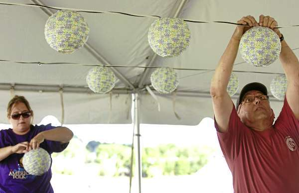 &quotIt always amazes me how an empty site becomes a festival so quickly,&quot said Roger Hicks (right) of Bangor as he volunteers setting up lights in the beer tent on Thursday, Aug. 26, 2010 in preparation for the American Folk Festival on the Bangor Waterfront. Helping Hicks is first-year volunteer Molly Lewis of Baltimore who said, &quotI'm loving it. It's good people and the weather's looking better.&quot (Bangor Daily News/Bridget Brown)