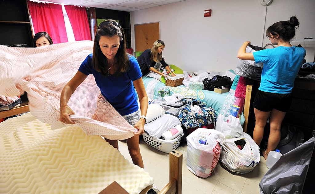 First-years students Whitney Callahan, right, of Rockport Mass. and her roommate Kelly Graham, left, of Merrimac N.H. get assistance from their mothers, Lisa Graham, second from left and Alison(cq) Callahan as the pair set up their dorm room at Oxford Hall on the University of Maine campus on Friday, August 28, 2010. (Bangor Daily News/Kevin Bennett)