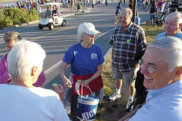 Volunteer Maria Hantala of Levant (center) collects donations from festival goers at the opening night of the American Folk Festival on the Bangor Waterfront on Friday, Aug. 27, 2010. (Bangor Daily News/Bridget Brown)