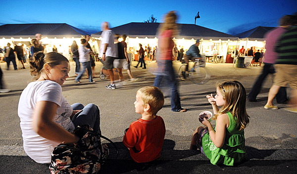 Ashlea McDonough of Hampden (left) tkes an ice cream break with her children William, 3, (center) and Scarlett, 5, Friday evening at the American Folk Festival in Bangor.  Ashlea said that they came to festival every year since it started even in 2009 when rain kept a lot of people away.
